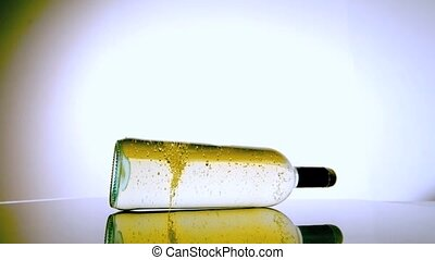 White wine bottle spinning around on white surface in slow...