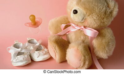 Pink soother falling in front of baby shoes and a teddy bear...