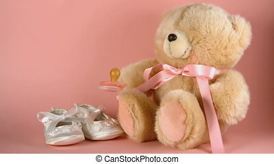 Pink soother falling onto a teddy bear and baby shoes in...