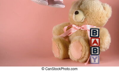 Baby shoes falling next to a teddy bear and baby blocks in...