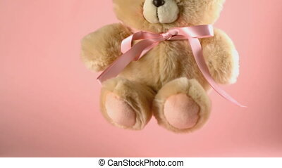 Teddy bear falling and bouncing on a pink surface in slow...