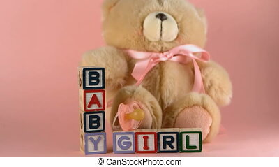 Teddy bear falling onto baby blocks
