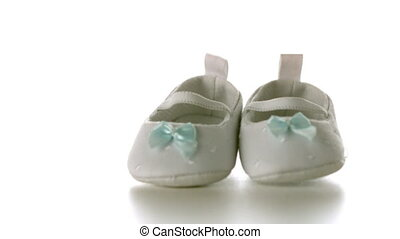 White baby shoes falling on white surface in slow motion