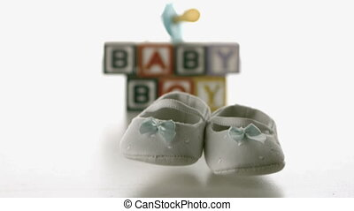 Baby shoes falling in front of blue