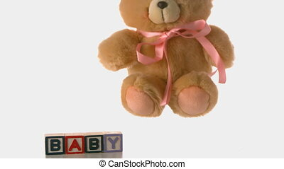 Teddy bear falling besides baby blo