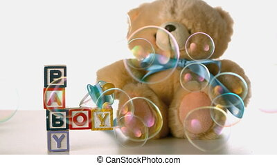 Bubbles floating over baby blocks soother and teddy bear in...