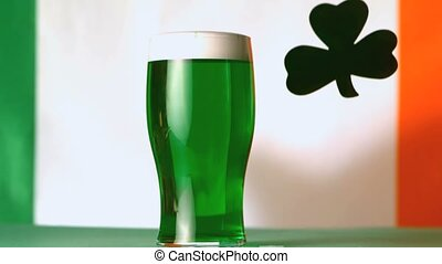 Large green shamrock falling beside pint of green beer in...