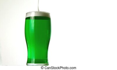 Foam pouring onto pint of green beer in slow motion