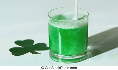 Green beer pouring into tumbler beside paper shamrock in...