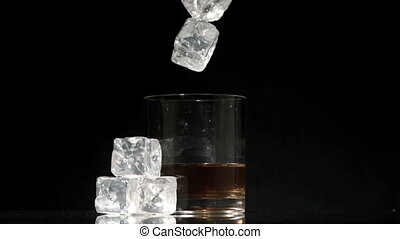 Ice cubes falling into glass of whiskey and ice on black...