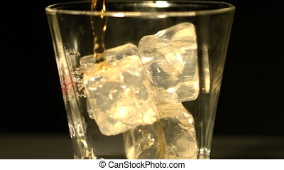 Whiskey pouring into tumbler with ice close up in slow...