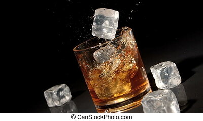 Three ice cubes falling into tumbler of whiskey and ice in...