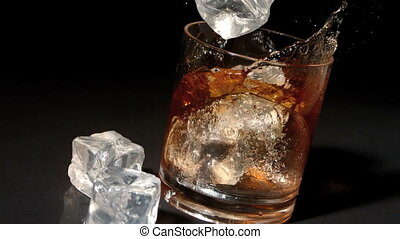 Ice cubes falling into tumbler of whiskey and ice in slow...