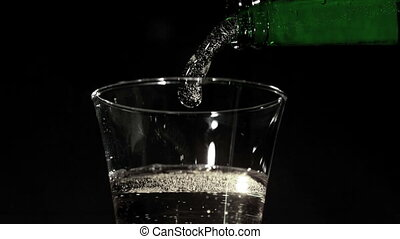 Bottle pouring fizzy water into glass in slow motion