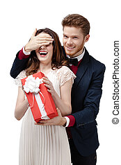 Man closes eyes of his girlfriend to give a present in red box