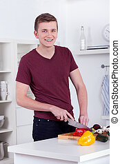 young man chopping vegetables for a meal in the kitchen