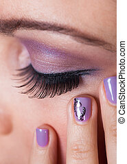 Close-up Of Womans Eye With Purple Eyeshadow And Finger Nail...