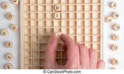 Hand spelling out diabetes message in wooden dice on grid in...