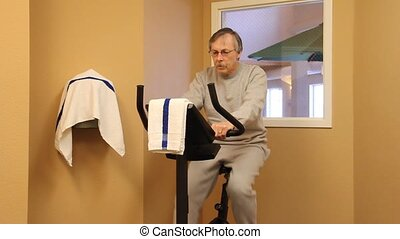 riding exercise bike - man riding an exercise bike