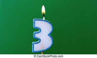 Three birthday candle flickering and extinguishing on green...