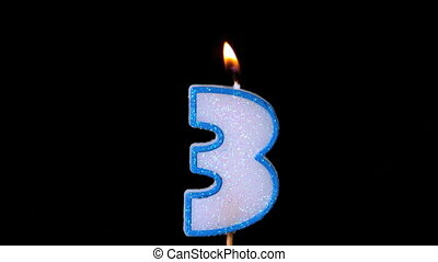Three birthday candle flickering and extinguishing on blue...