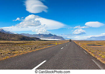 Highway through South Icelandic landscape under a blue...