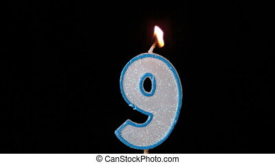 Nine birthday candle flickering and extinguishing on black...