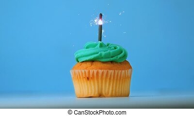 Sparkler burning on blue birthday cupcake in slow motion