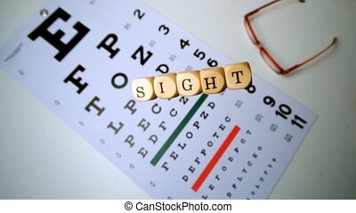 Dice spelling out sight falling onto eye test beside glasses...