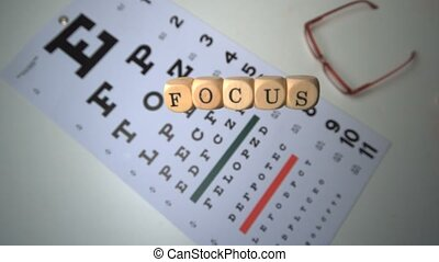 Dice spelling out focus falling onto eye test beside glasses...