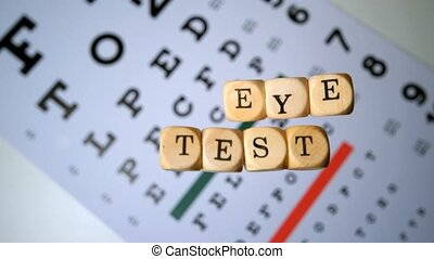 Dice spelling out eye test falling onto eye test beside...
