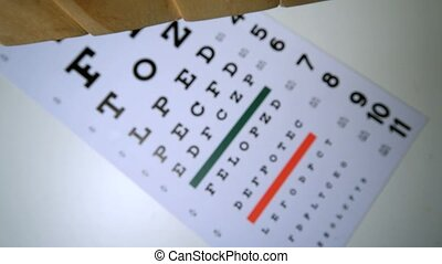 Blocks spelling out sight falling onto eye test in slow...