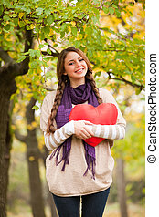 Girl with toy heart at autumn park