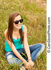 Beautiful teen girl in the park at green grass.