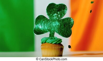 Shamrock confetti falling on st patricks day cupcake close...
