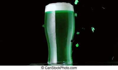 Shamrock confetti falling in front of pint of green beer on...