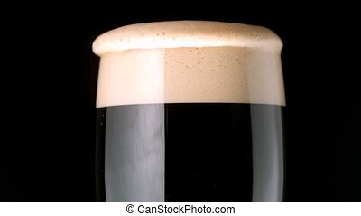 Foam head settling on pint of stout on black background in...