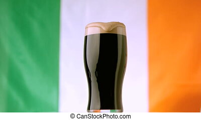 Head of pint of stout spilling over on flag of ireland...