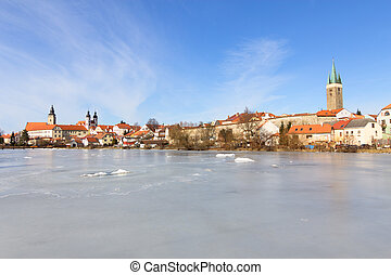 Historic city of Telc in winter with a frozen pond in the...
