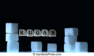 Dice spelling out sugar falling beside sugar cubes in slow...