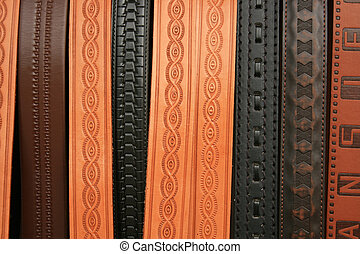 Stamped Belts - Embossed and stamped leather belts hang for...