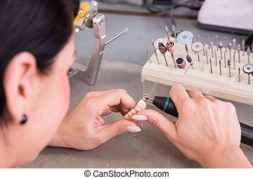 Technician at work in a dental lab or workshop producing a...