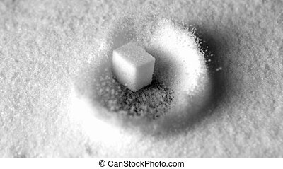 Sugar cube falling in pile of sugar in slow motion