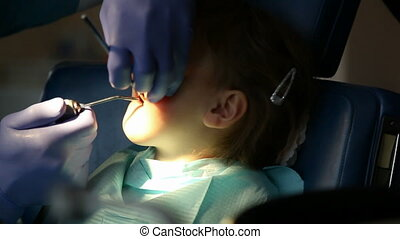 dentist - little girl in the dentist treats tooth
