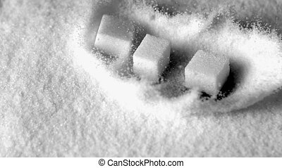 Sugar cubes falling in pile of sugar in slow motion