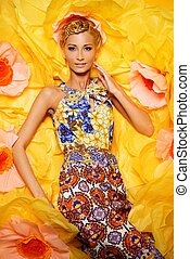 Beautiful young blond woman in colourful dress lying among...