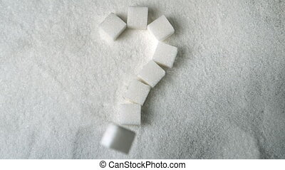 Question mark spelled out in sugar cubes forming on pile of...