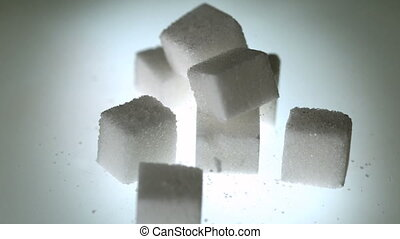 Sugar cube falling onto pile of cubes in slow motion