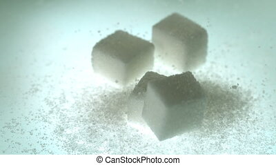 Sugar cube falling onto pile of cubes and powder sugar in...