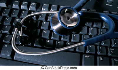 Stethoscope falling onto computer keyboard in slow motion